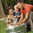 Stock Photo: Family giving dog a bath.