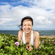 Woman Lying in Plants Near Beach - Stock Photo