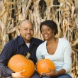 Couple holding pumpkins. — Stock Photo