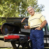 Senior man grilling by RV. — Stock Photo