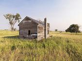 Zniszczony dom w dziedzinie. — Zdjęcie stockowe