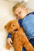 Baby sleeping with bear. — Stock Photo