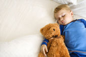 Child sleeping with bear. — Stock Photo