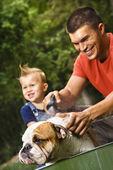 Family giving dog a bath. — Stock Photo