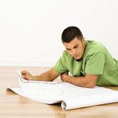 Man reading blueprints. — Stock Photo