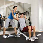 Woman spotting man at gym — Stock Photo