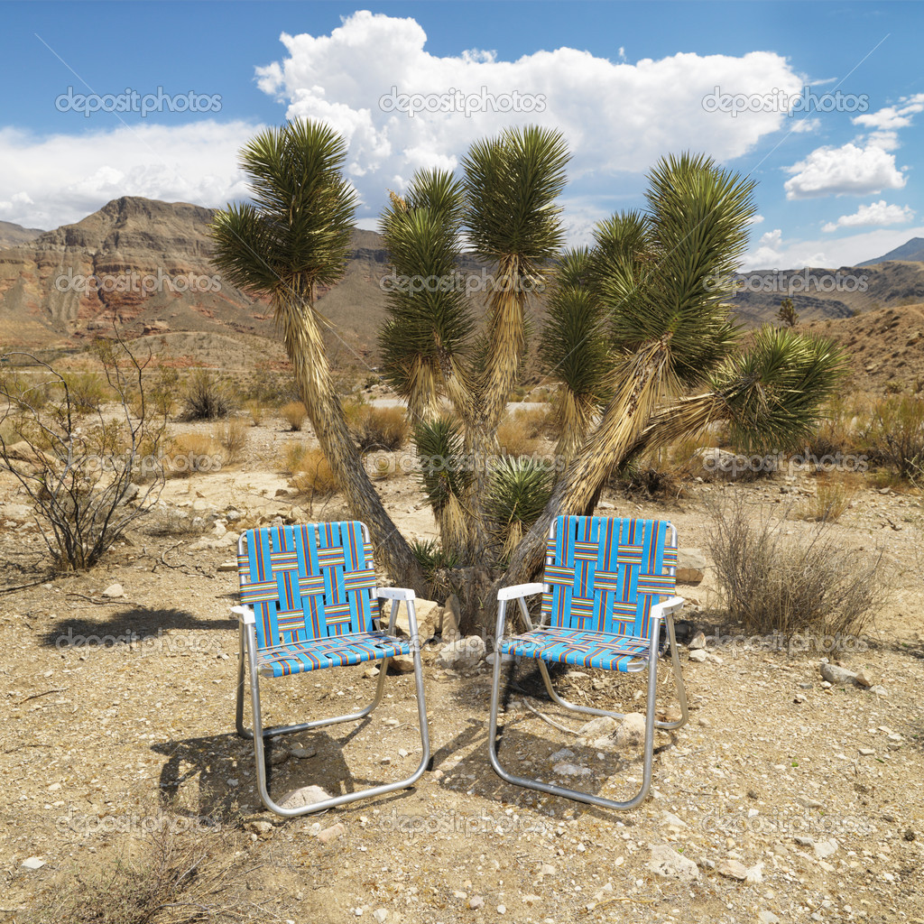 Empty plaid lawn chairs in desert landscape. — Stock Photo #9301173