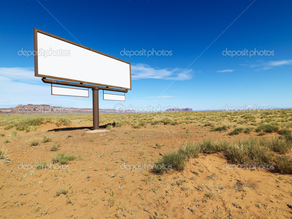 Blank billboard in middle of desert landscape with distant mountains.  Stock Photo #9301994