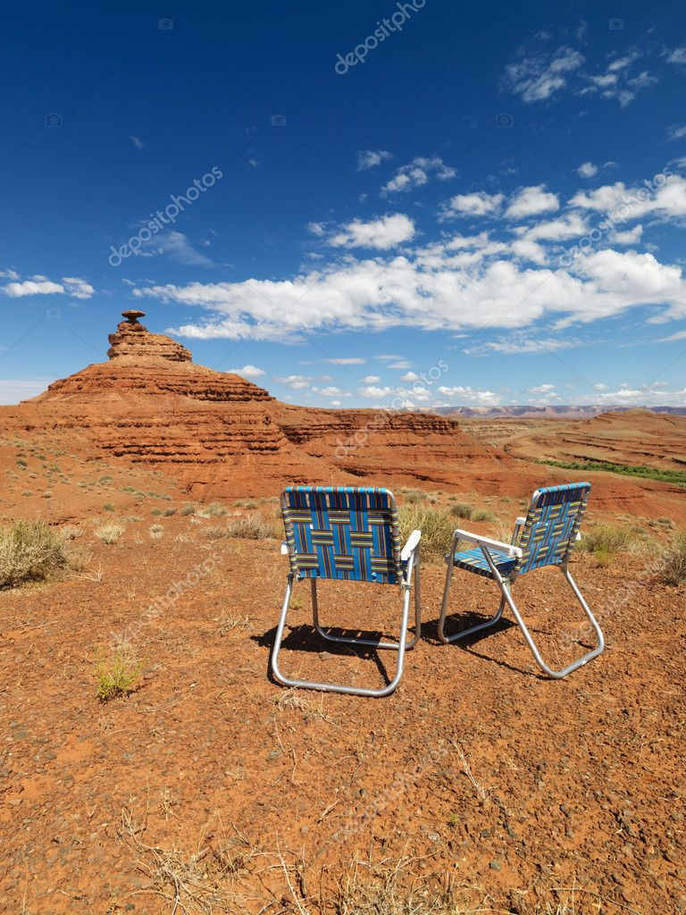 Two outdoor lawn chairs in scenic desert landscape with mesa land formation. — Stock Photo #9302044