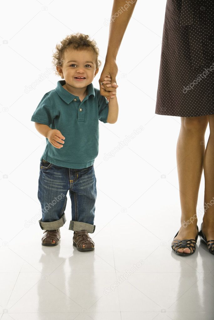 African American toddler boy holding onto mothers hand smiling at viewer. — Stock Photo #9305568