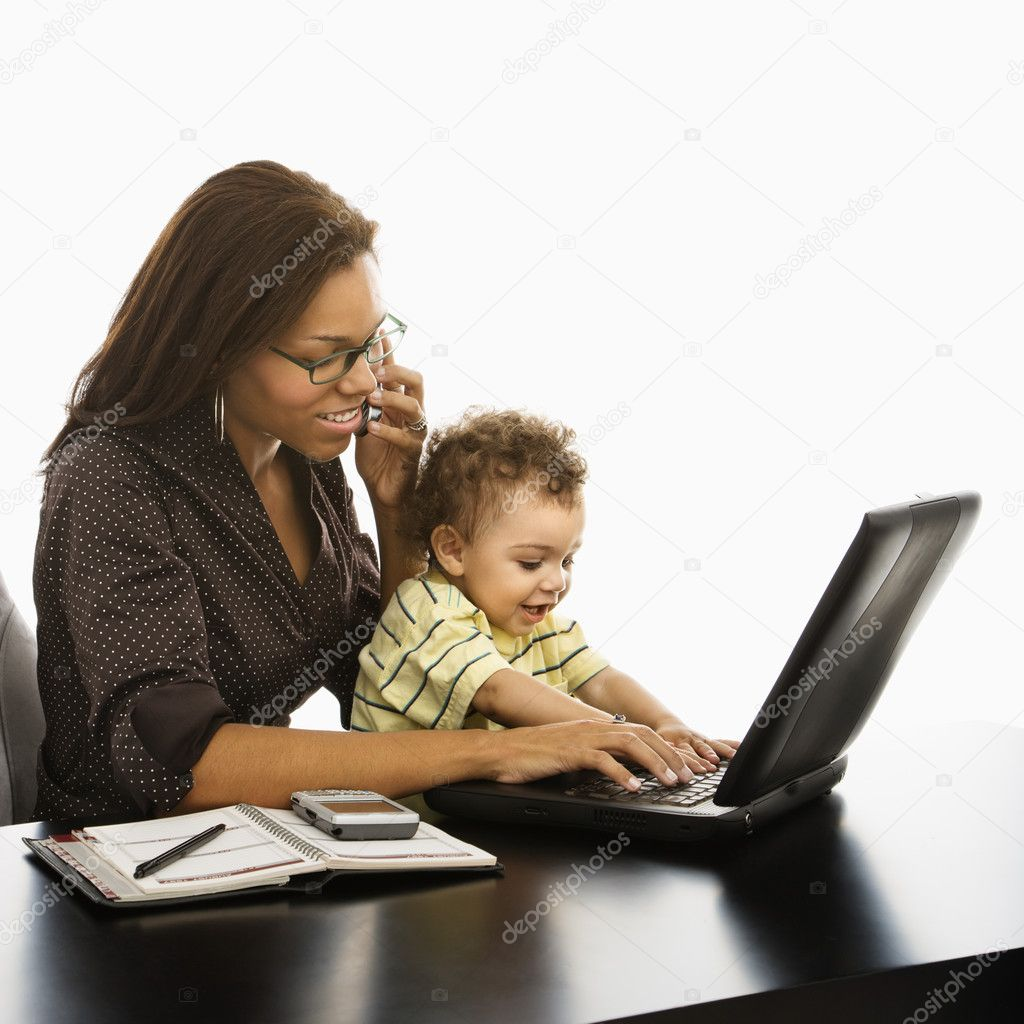 African American businesswoman at work on laptop and cell phone with toddler son on lap.  Foto de Stock   #9305586