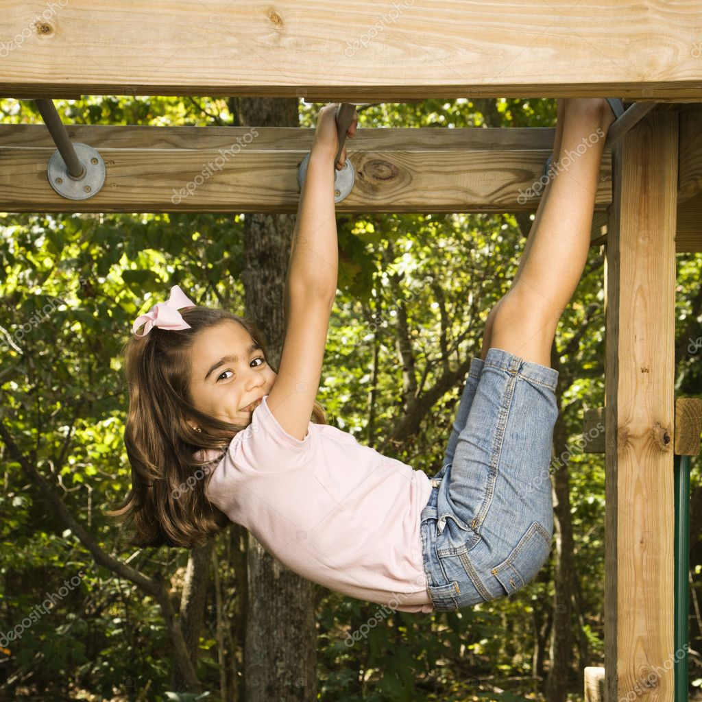 Side view of Hispanic girl hanging by arms and legs from monkey bars smiling at viewer. — Stock Photo #9306087