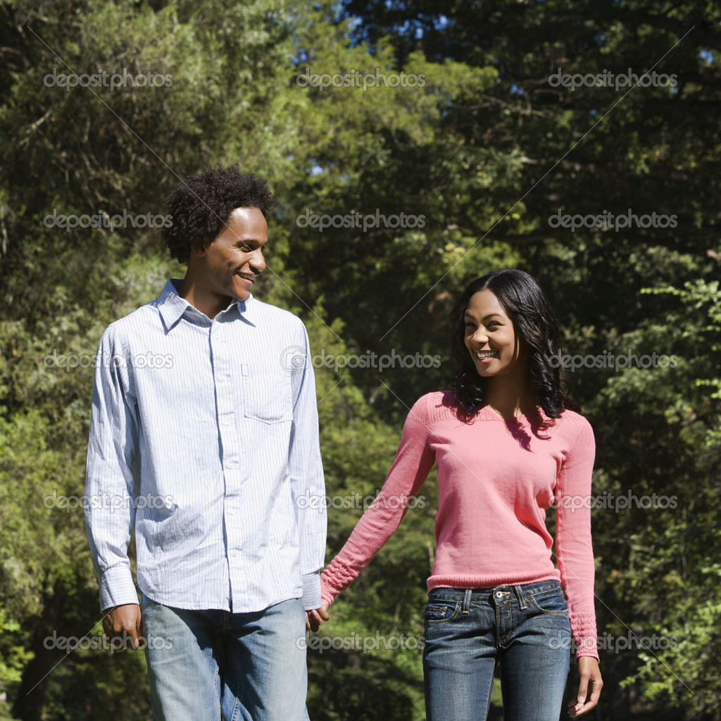 Smiling couple holding hands walking and talking in park. — Stock Photo #9306167