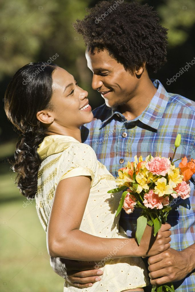 Woman holding flower bouquet and embracing man as they smile at eachother. — Stock Photo #9306262