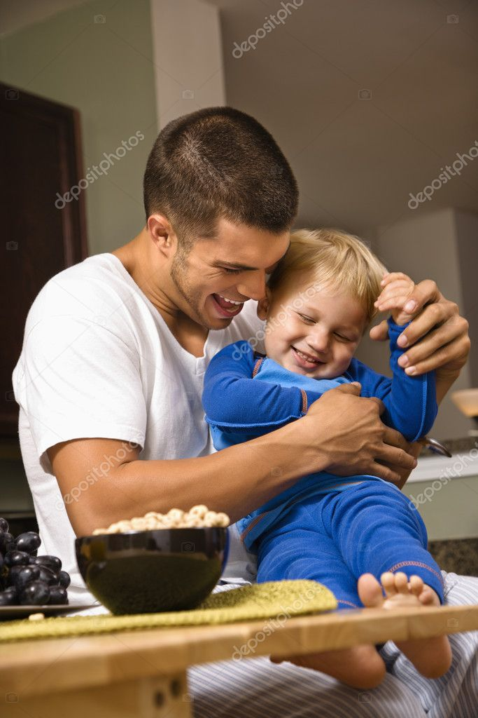 Caucasian man tickling toddler son in kitchen. — Stock Photo #9306349