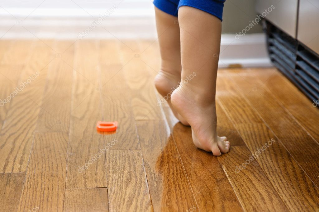 Feet of Caucasian toddler boy with magnets in front of refrigerator.  Stock Photo #9306361