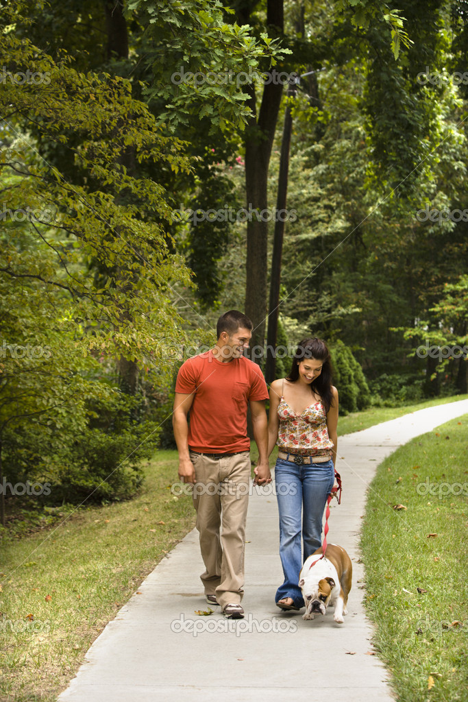 Caucasian mid adult couple walking English Bulldog in park.  Stock Photo #9306546
