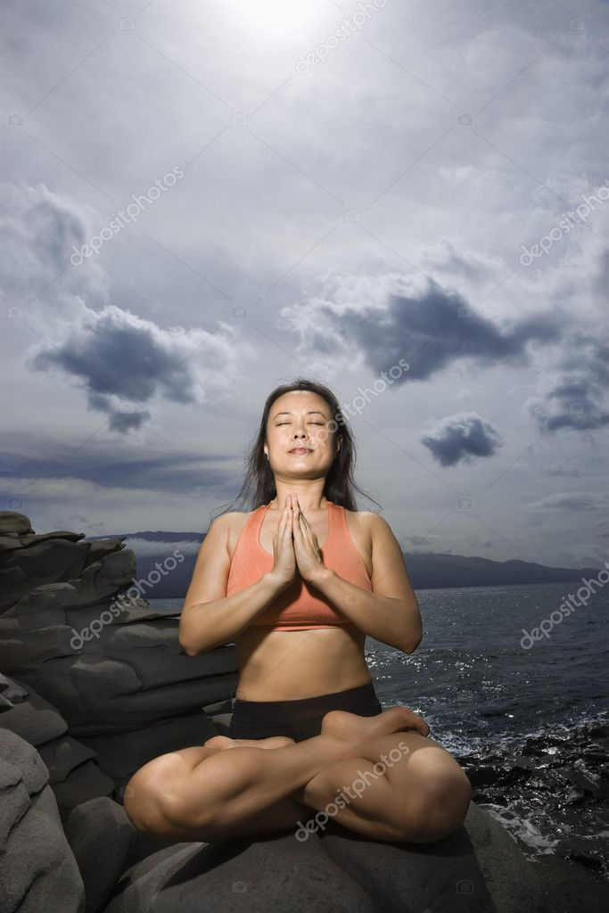 Asian woman sitting on rock by ocean in lotus pose with eyes closed in Maui, Hawaii  Stock Photo #9306649