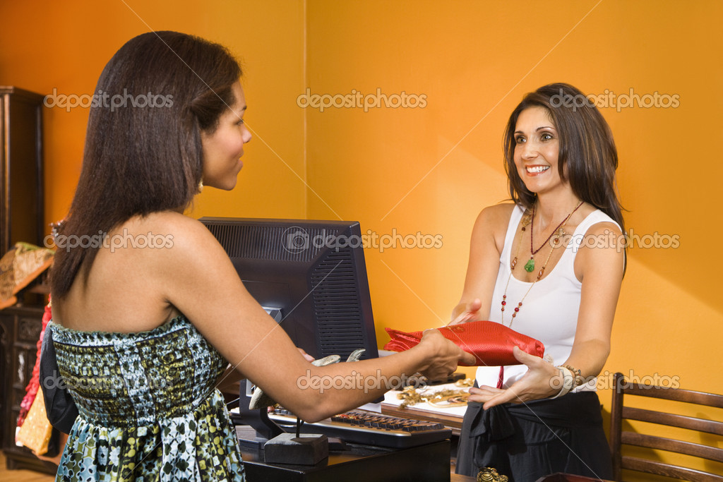 African American women handing item to sales clerk in boutique.  Stock Photo #9306750