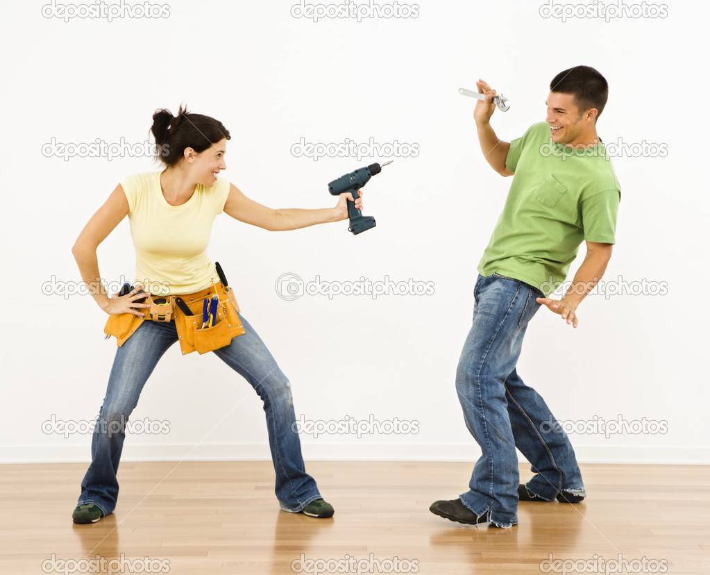 Woman pointing drill playfully at man smiling and laughing in home. — Stock Photo #9306927