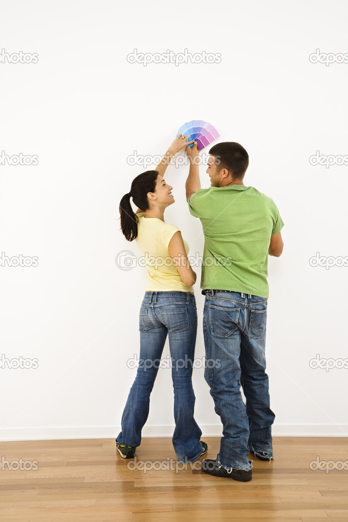 Attractive young adult couple holding color paint samples up to white wall. — Stock Photo #9306955
