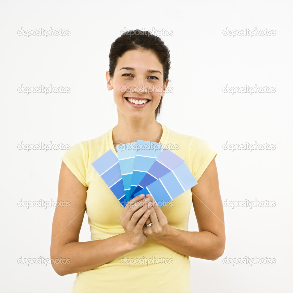 Pretty woman smiling holding out paint sample cards.  Stock Photo #9306958