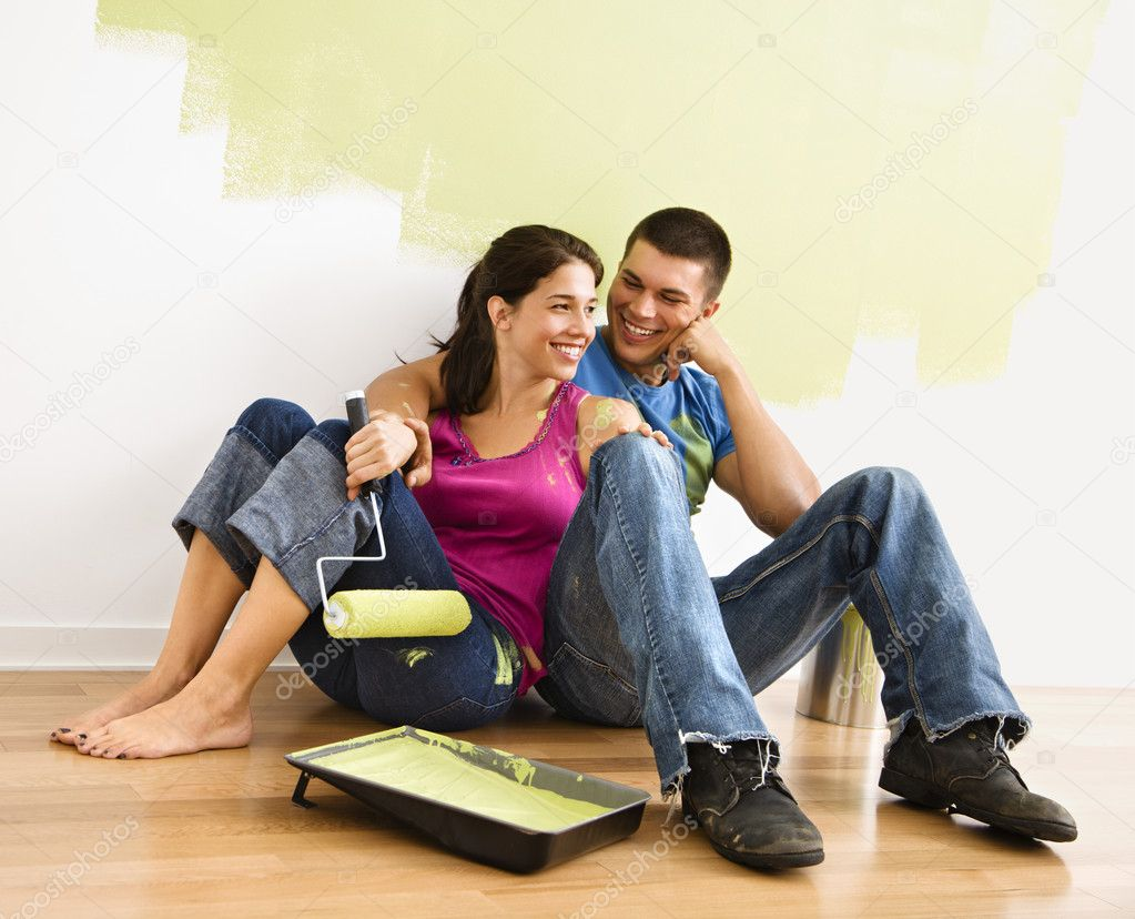 Couple sitting on floor smiling in front of partially painted wall in home. — Stock Photo #9307010
