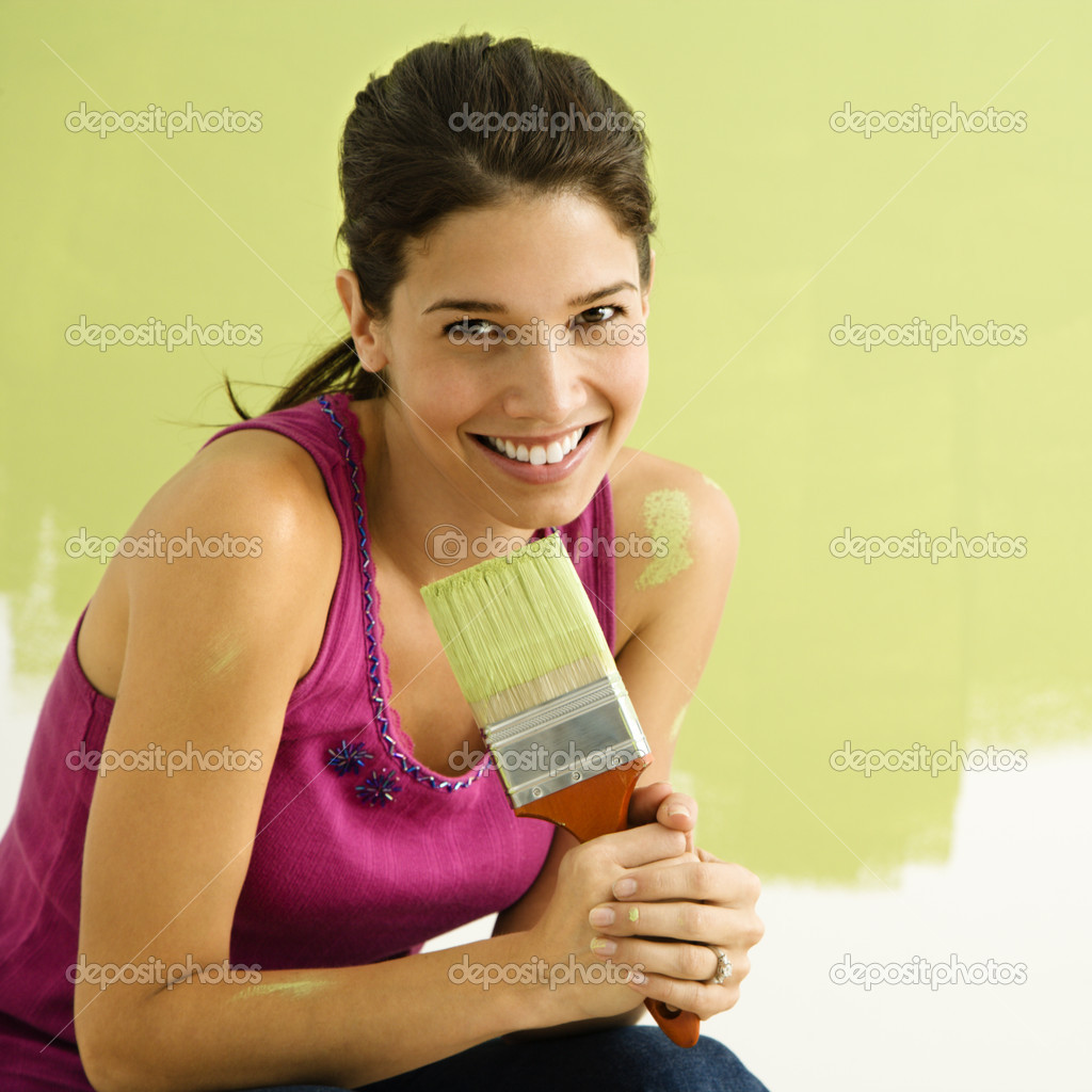 Pretty smiling woman kneeling in front of partially painted wall holding paintbrush. — Stock Photo #9307012