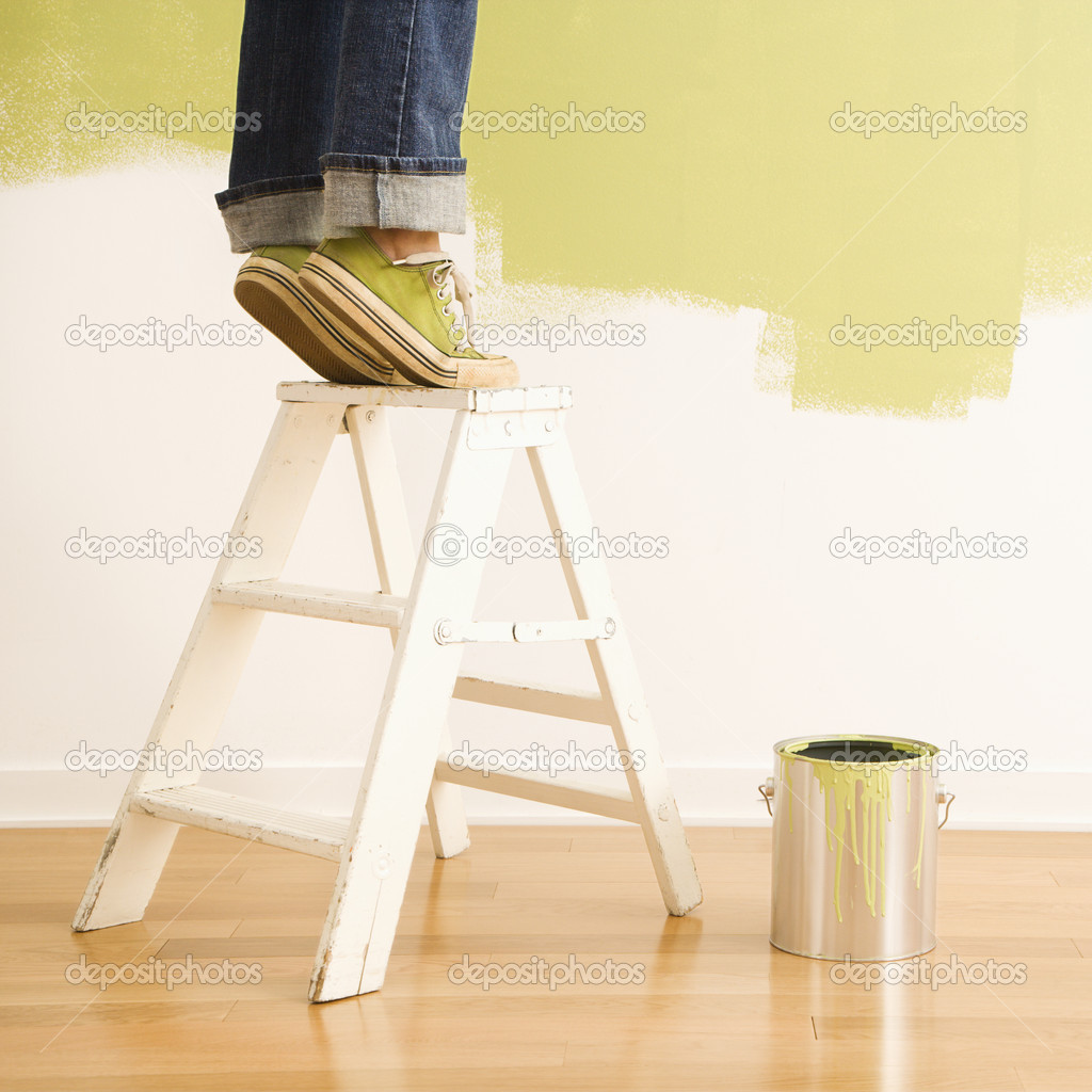 Legs of woman standing on tiptoe on stepladder with paint can and painted wall. — Stock Photo #9307061