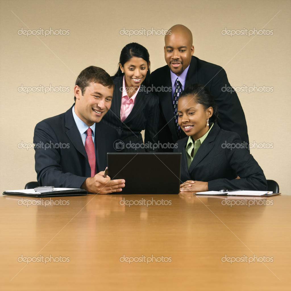 Businesspeople gathered around laptop computer looking at monitor and smiling. — Stock Photo #9307219