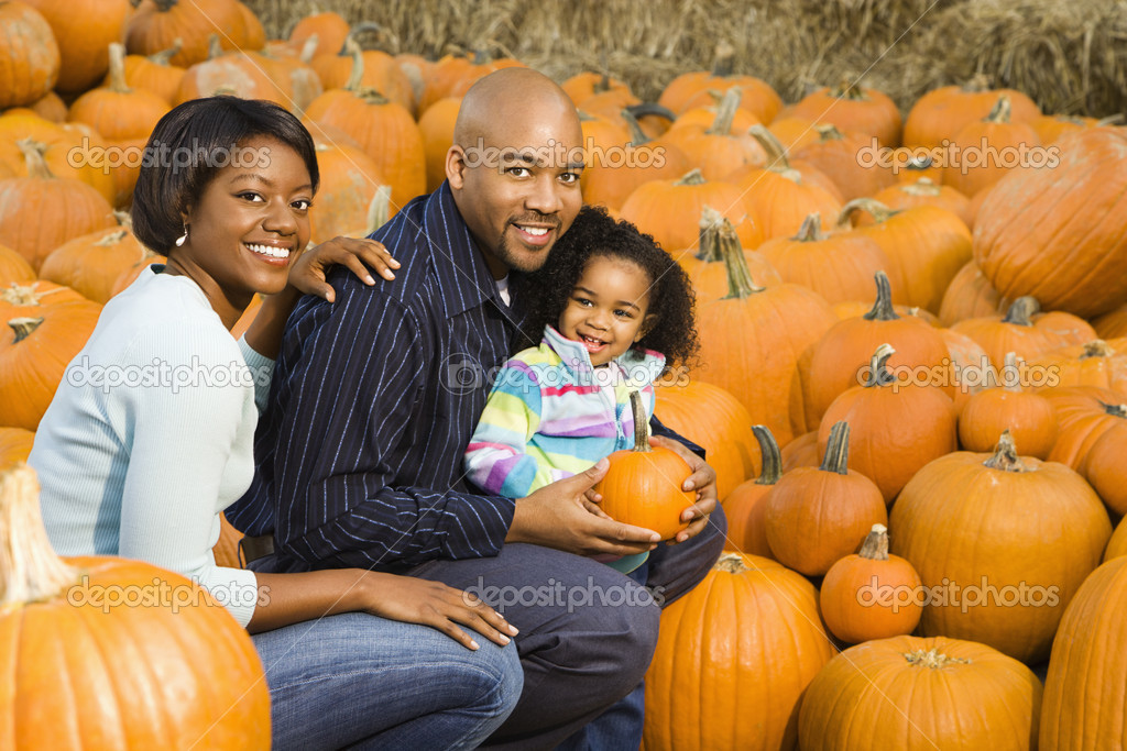 Parents and daughter picking out pumpkin and smiling at outdoor market. — Stock Photo #9307336