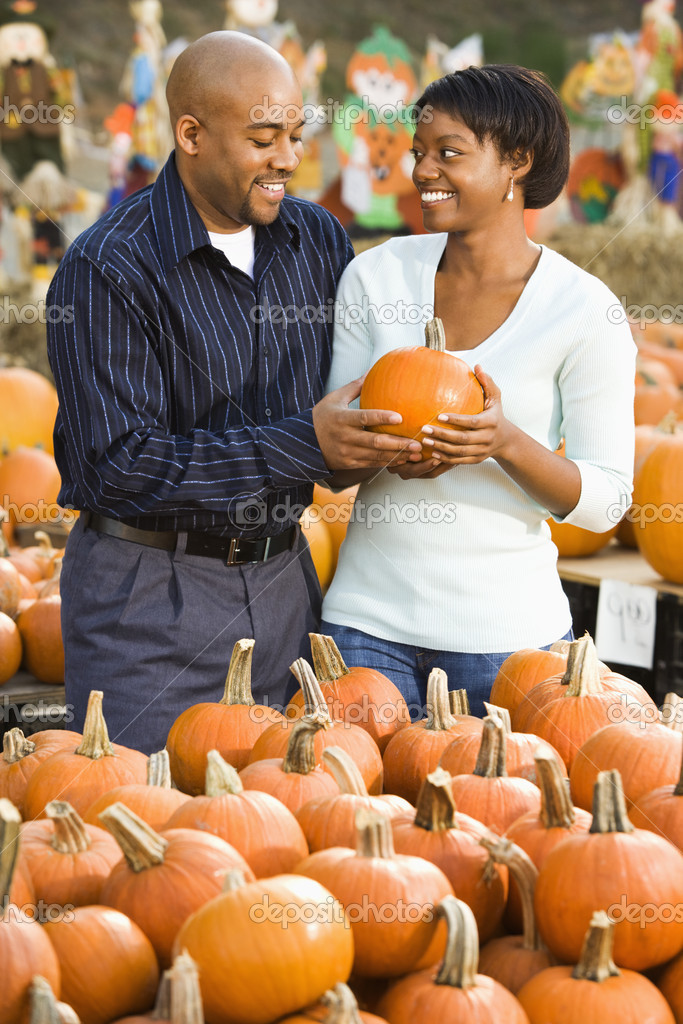 Couple picking out pumpkins and smiling at outdoor market. — Stock Photo #9307344