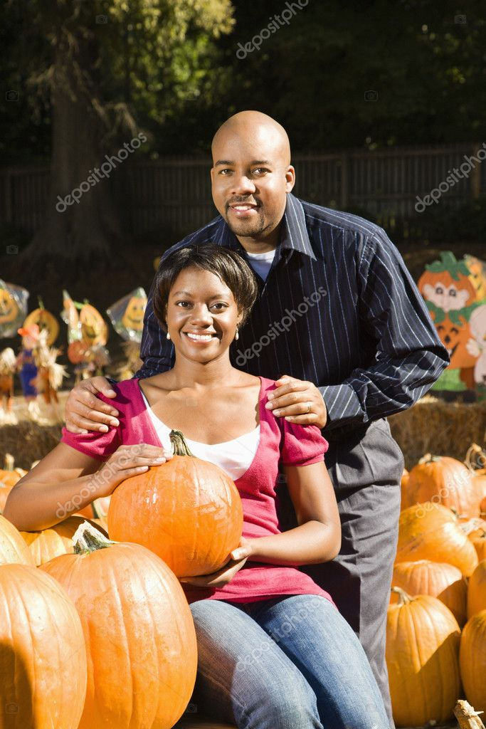 Portrait of happy smiling couple sitting in pumpkins at outdoor market. — Stock Photo #9307369