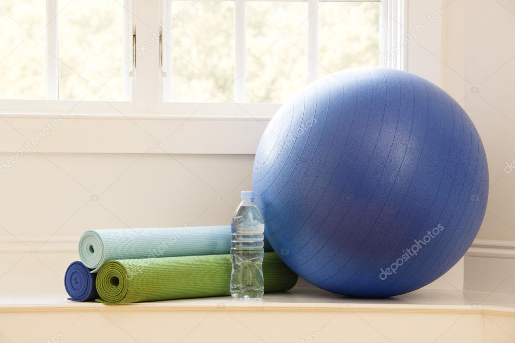 Balance ball, exercise mats and bottled water at gym by window. — Stock Photo #9309592