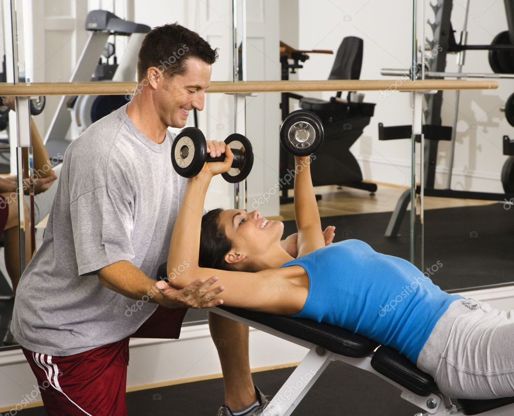 Man assisting woman at gym with hand weights smiling. — Stock Photo #9309682