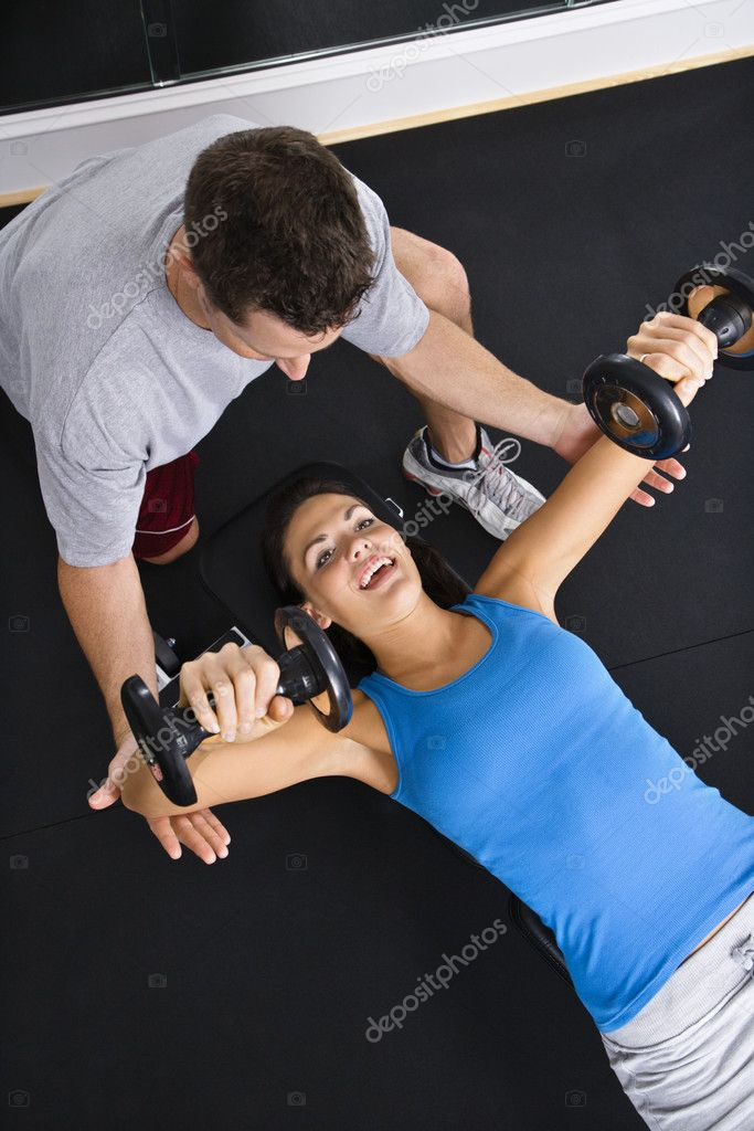 Man assisting woman lifting weights at gym. — Stock Photo #9309698