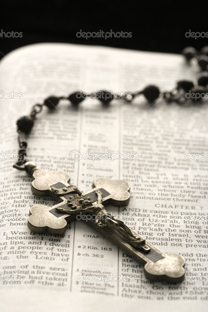 Rosary with crucifix lying on open Bible.  Stock Photo #9309824
