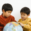 图库照片: Boys looking at globe