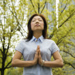Woman meditating outdoors - Stock Photo
