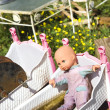 Baby doll in crib. - Stock Photo