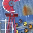 Windmill against blue corrugated metal building. - Stockfoto