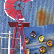 Windmill against blue corrugated metal building. - Stock Photo