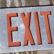 Exit sign on wood - Stock Photo