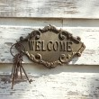 Welcome sign on wall. - Stock Photo