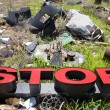 Letters spelling STOP in trashy junkyard. - Stock Photo