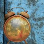 Alarm clock against blue. — Stock Photo