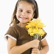 Little smiling hispanic girl with flowers. — Stock Photo