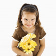Cute little hispanic girl with bouquet. — Stock Photo