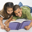 Brother and sister reading book together. — Lizenzfreies Foto