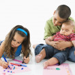 Hispanic girl coloring with brothers. — Stock Photo #9312188